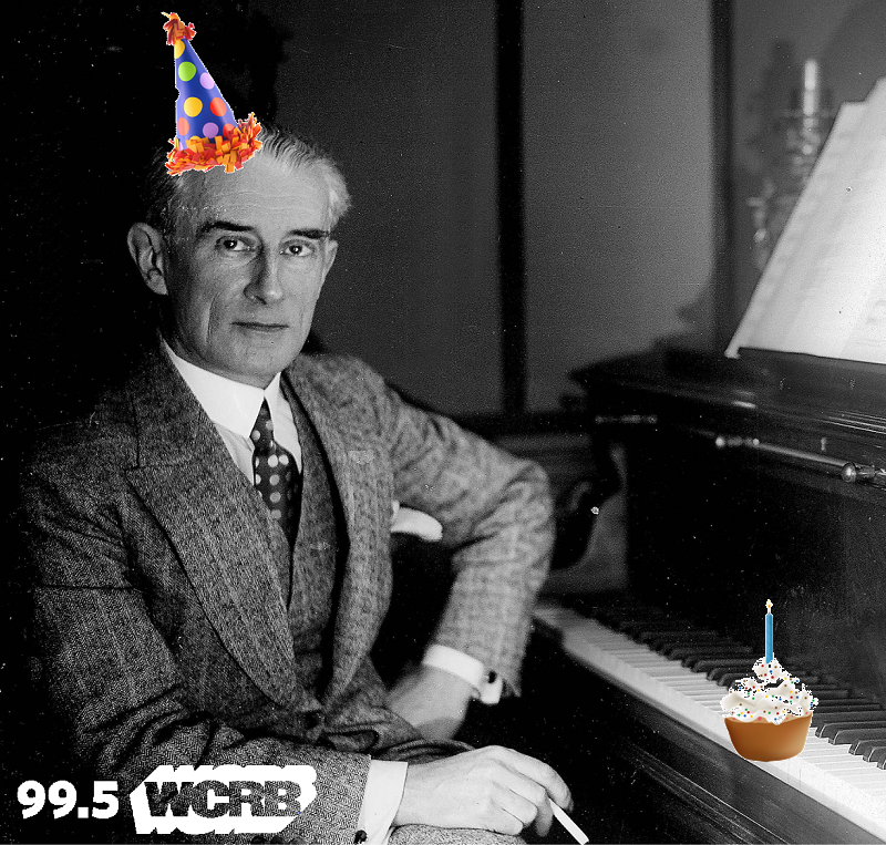 Maurice Ravel, seated at a piano, with a birthday hat