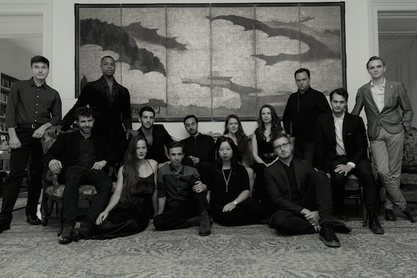 The 17 members of the American Modern Opera Company sit before a tapestry