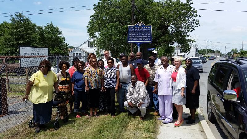 Former Richard Allen School students and family members, including state legislators, pose in front of the new historic marker in Georgetown.