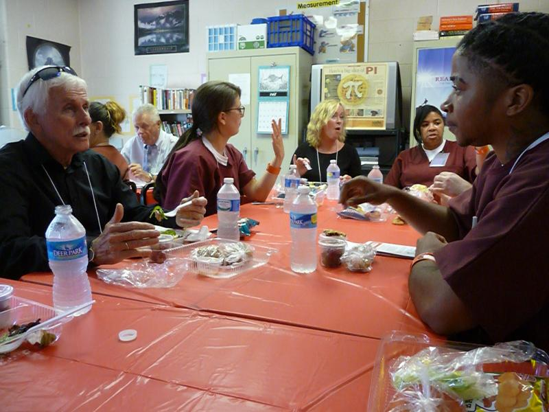 Inmates, including Lakisha Short at right, eat lunch with guests in an adult education classroom at the prison.