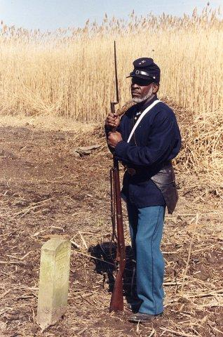 Willis Phelps, president of the friends group that's helped restore the African American Union Church Cemetery, poses as a soldier from the U.S. Union army's Colored Troops.