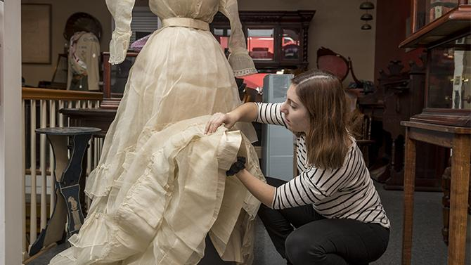UD students clean and assess an 1870s Quaker wedding gown.