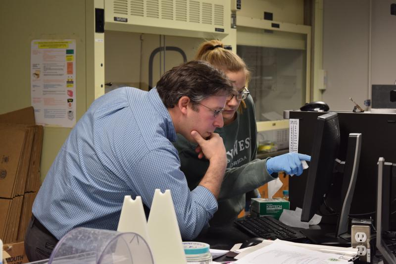 Jonathan Cohen and lab technician Haley Gloss look at microplastics distributions on a computer.