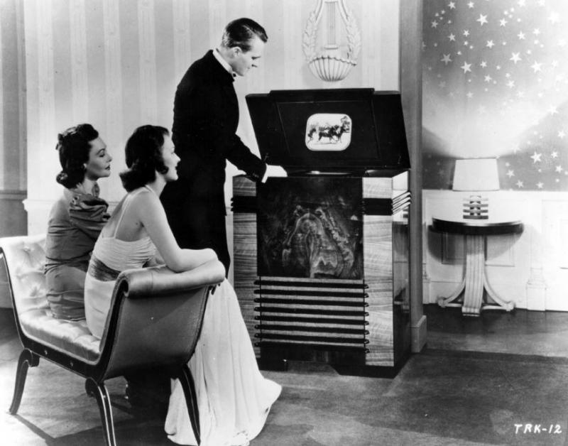 This publicity photograph from RCA emphasizes the wealth and prestige of the first television viewers posed in front of the TRK-12 RCA receiver