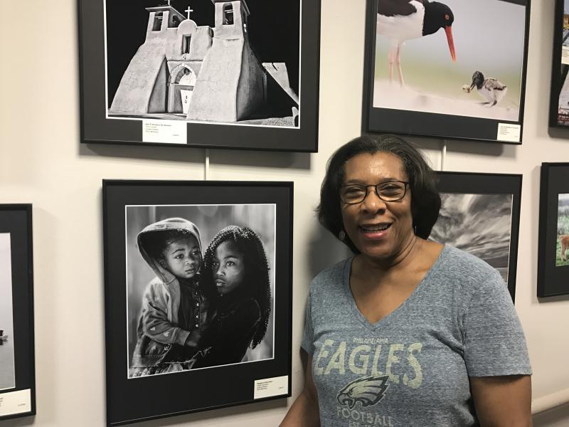 Helen Gerstein stands next to one of her photographys in the WIEP exhibition.