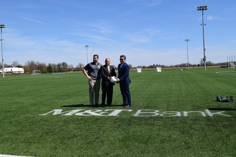 DE Turf Executive Director Chris Giacomucci (left) stands with M&T Bank's Nick Lambrow and Bill Strickland (right) from DE Turf's Board of Directors after unveiling Field 2's sponsorship.