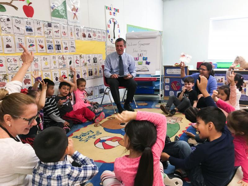 Gov. John Carney (D) reads to pre-schoolers at Wilmington's Latin American Community Center after announcing a new federal grant award.