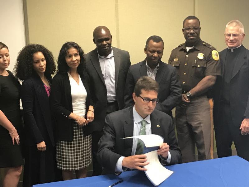 New Castle County Executive Matt Meyer - surrounded with immigration advocates - signs an executive order pertaining to immigration Wednesday.