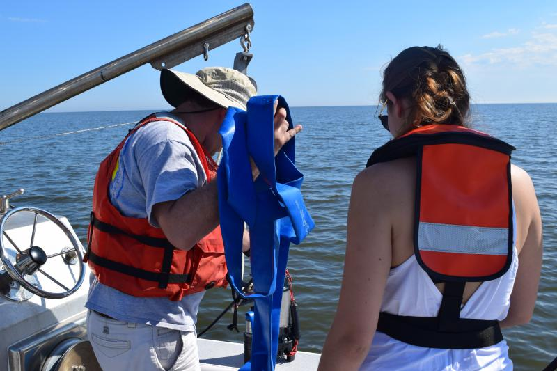 Jonathan Cohen and Talene Yeghissian prepare to toss a pump into the water to sample for microplastics.