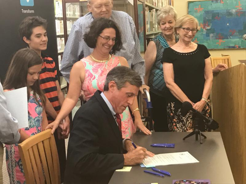 Delaware Governor John Carney signs two library-related bills Wednesday afternoon in Newark.