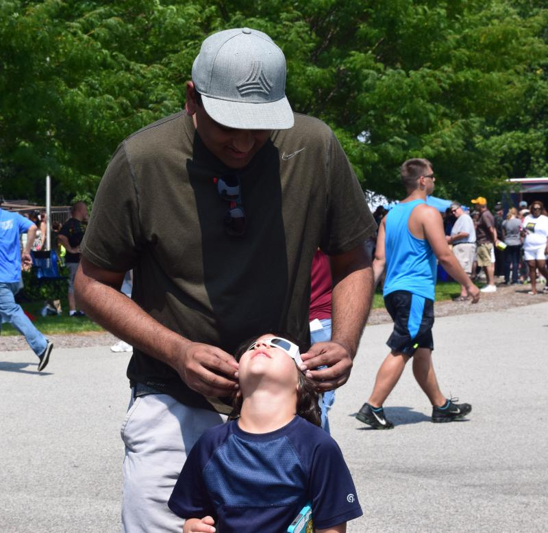 Chaitanya Vardhana from Portland, OR holds a pair of eclipse glasses on his son as he stares up at the sky at Big Oak Park in Smyrna.