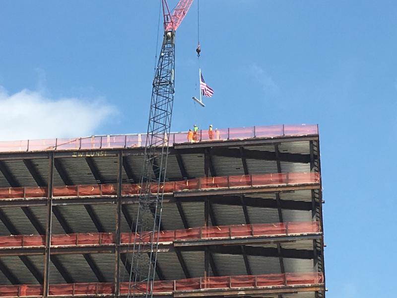 """Workers put the final beam of the STAR Tower in place as part of the building's """"topping off"""" ceremony"""