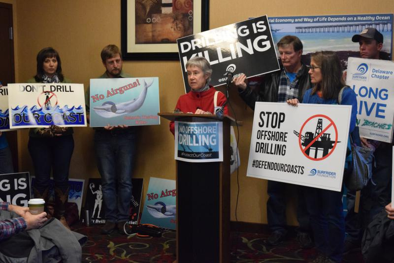 Environmentalists hold up signs opposing offshore drilling.