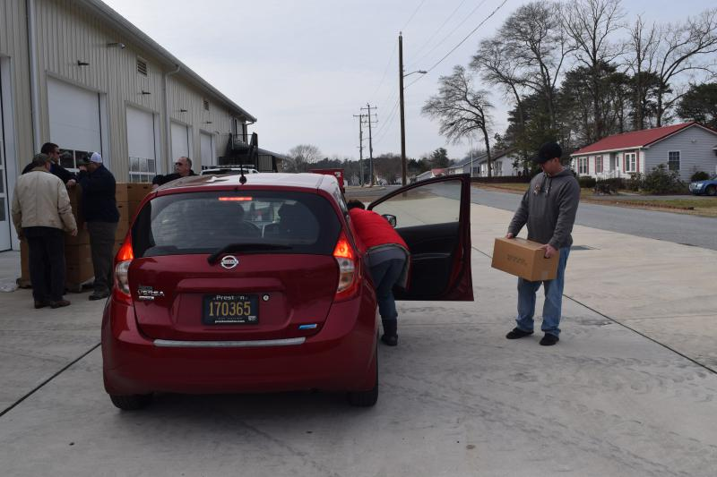 Volunteers help load cases of water into a resident's car.