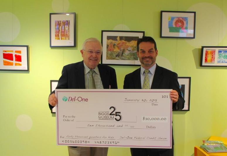 "Del-One CEO Dion Williams (right), presents Biggs Museum Executive Director Charles Guerin (left), with a $10,000 check to kick off the ""Quarters for Kids"" program."