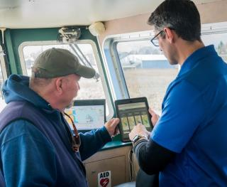 UD's Matt Oliver (right) shows R/V First State Captain Mike Garvilla the alert system.