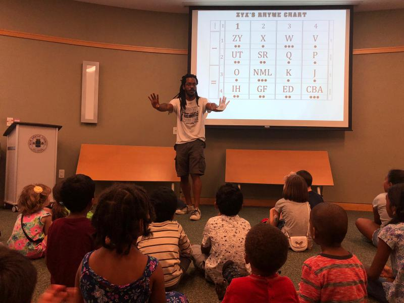Baba Bomani teaches kids about hip hop rhythms by using the alphabet as an example