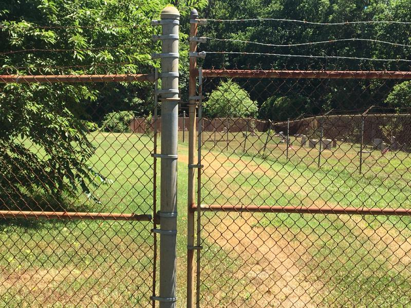 The Fork Branch School site is visible behind a chainlink fence