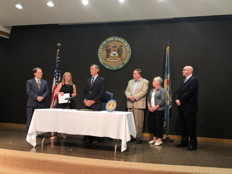 Barb and Marty Wright join legislators and Gov. Carney as he signs the bill into law