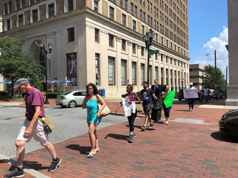 Protesters march to the site of a Buccini/Pollin ribbon cutting