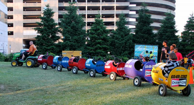 Children taking a ride on tractor-pulled carts.
