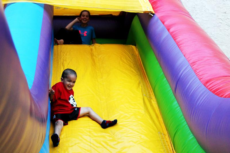 Kids taking turns on the inflatable slide.
