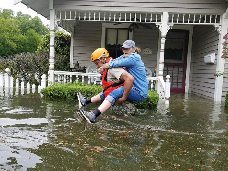 A Texas National Guard soldier carries a woman out of a flooded building during rescue operations in Houston, Texas.