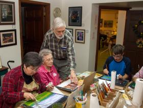 Hal Davis, standing, a co-owner of Paint Lick Community Arts Center, helped Helen Starnes, 86, during a painting class Monday. Starnes, the oldest student in the class, came with daughter Brunette Arnold, left. Home-school student Joey Roush, 14, right, was the youngest in the group.
