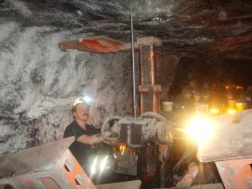 Mackie Bailey in the P-1 Mine. The roof bolting machine's safety devices are visible in the foreground of the photo; law requires they be held against the roof.