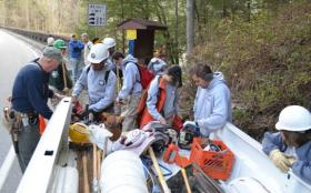 Members of an AmeriCorps crew and other volunteers gather tools as they prepare to work on a trail at Cumberland Falls State Resort Park.