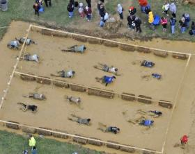 Participants in last year's Tough Mudder event crawl through mud and under electric wires in one of the many obstacles. The Tough Mudder event will return again in October.