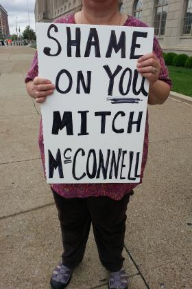 A protestor holds a sign calling on Sen. Mitch McConnell, R-Ky., to support gun background checks legislation