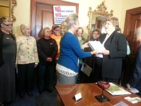 The governor's secretary, Debi Gall, receives the petition from Sister Claire McGowan.