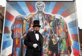 Abraham Lincoln presenter Jim Sayre stood near the new Lincoln mural on Water Street in Lexington. It was painted last month by Brazilian artist Eduardo Kobra on the 60-foot-tall back wall of The Kentucky Theatre building.