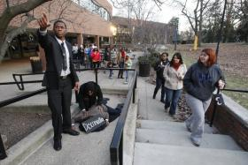 Jillian Pyatte, right, watched as Alpha Phi Alpha members Jared Scott, left, T.J. Merritt and Rashad Bigham re-created the scene of Martin Luther King Jr.'s assassination as people passed during a silent march to commemorate the legacy of the civil rights leader.