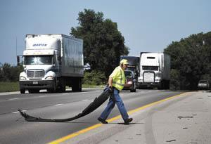 Jim Elliott of Scottsville, a safety patrol officer with the Kentucky Transportation Cabinet's Division of Incident Management, pulls a piece of tractor-trailer tire from the middle of Interstate 65. Elliott patrols 58 miles of I-65, from the Tennessee bo