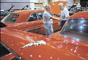 Bill Sammons (left) of Lexington and Clarence Stanley of Sylvania, Ohio, talk about the similarities between Pontiac and Chrevrolet car tops Thursday during the 2011 Pontiac-Oakland Club International Convention at the Sloan Convention Center.