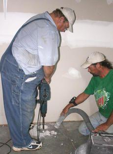 Alan New and Joey Weller of Sapper6 Inc. drill a hole for a radon mitigation system in a home in the Fox Fire subdivision in Elizabethtown.