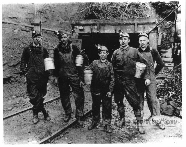 Miners pose at mine entry in Lynch after work. Round lunch pails are triple-tiered to hold both food and water. Carbide lamps are mounted atop soft headgear which actually only served to hold the lights and offered no protection.