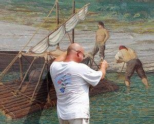 Herb Roe touches up a mural Saturday, near Limestone Landing in Maysville.