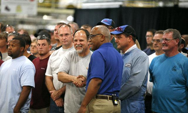 Wil James, center foreground, president of the Georgetown Toyota plant, shook hands with team members before a live webcast last month to introduce the redesigned 2012 Camry. After four years away from Georgetown, James is glad to be back at the plant.
