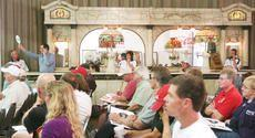 A phone bid is relayed to the auctioneer as others stay on the line with other bidders Sunday during the first live auction event of the Schmidt Museum of Coca-Cola Memorabilia at the museum in Elizabethtown.