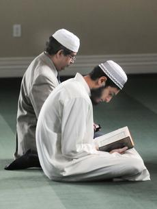 A pair of men read from the Qur'an as part of their prayers during Friday's Jumma Prayer at the Islamic Center in Elizabethtown.