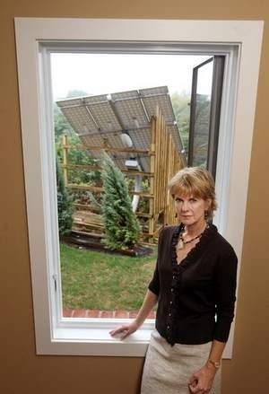 Becky Bush in a staircase of her new home on Wiedemann Hill, Newport, with a view of the large solar panel her neighbor has installed on his property behind her.