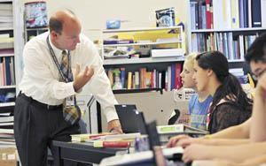 Gary Fields, principal at Bowling Green High School, talks to students Amy Cherry (left) and Claire Samuels during their freshman AP world history class Sept. 13.
