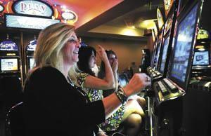Robin Harden (from left), Felecia Hudson and Janelle Barany, all of Bowling Green's Sun Suites Salon and Spa, play the new instant racing games Wednesday at Kentucky Downs in Franklin.