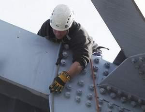 "Jeff Sams, a Kentucky Cabinet of Transportation bridge inspector, checks structural steel near a gussett plate atop the Carroll Cropper Bridge between Indiana and Boone County. The bridge is undergoing a ""fracture critical inspection."""