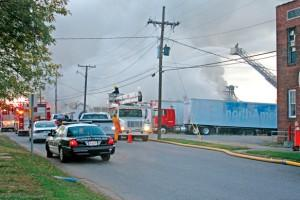 Crews battle a fire at Ellis Popcorn in Murray. Smoke rises above the building early Tuesday morning.