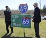 Kentucky Governor Steve Beshear, right, and Federal Highway Administration Administrator Victor Mendez, left, unveil the new Interstate 69 sign signaling a 38 mile section of the Western Kentucky Parkway to be designated as I-69 in Nortonville, Ky.