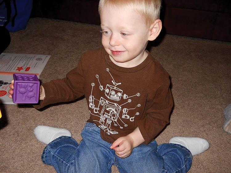 Caleb Hisle plays with colored blocks as part of the HANDS program for first-time parents. The program teaches parents how to interact and bond with their children.